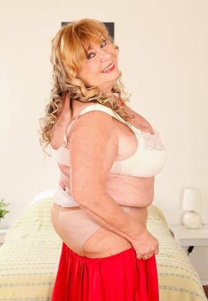 Aged Adult bbw squeezes heavy boobs in a bra after shades long red skirt