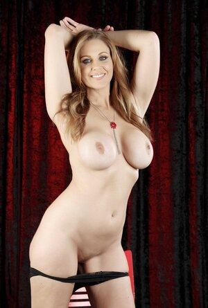 Good-looking female with big tits demonstrates shaved pussy sitting on red chair