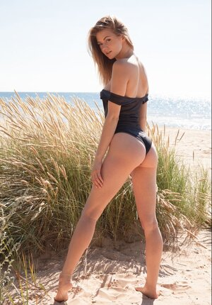 Phenomenal performer takes off one-piece swimsuit and besides poses on a windy day