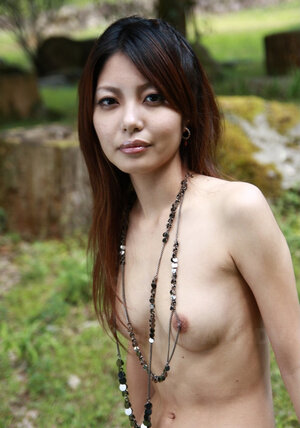 Beautiful asian lassie walks alone and slowly unclothes on camera