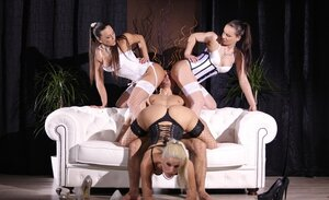 Three dominatrixes have an obedient sex thrall who helps them relax in a sex way